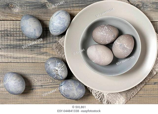 Natural dyed grey Easter eggs in bowl and plate on rustic grey wooden background. Top view point
