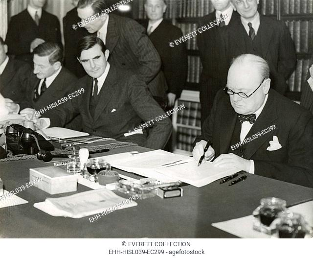 Winston Churchill signing the 'Lend Lease' agreement to lease British bases to the U.S. March 11, 1941. From his desk at 10 Downing Street, Churchill and U