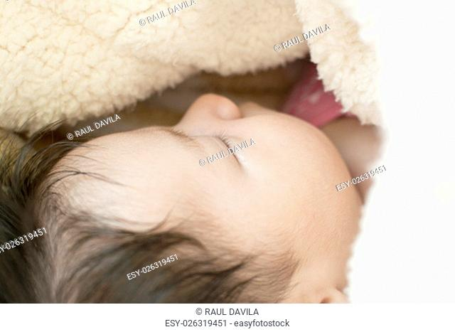 Little newborn girl sleeping on his back, covered by a blanket of fluffy