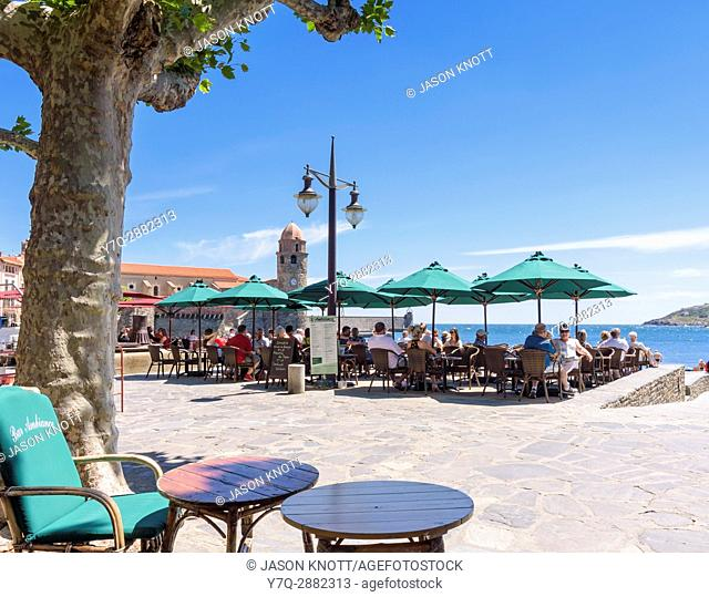 Beachside cafes overlooked by the bell tower of the Church of Notre Dame des Anges, Collioure, Côte Vermeille, Céret, Pyrénées-Orientales, Occitanie, France