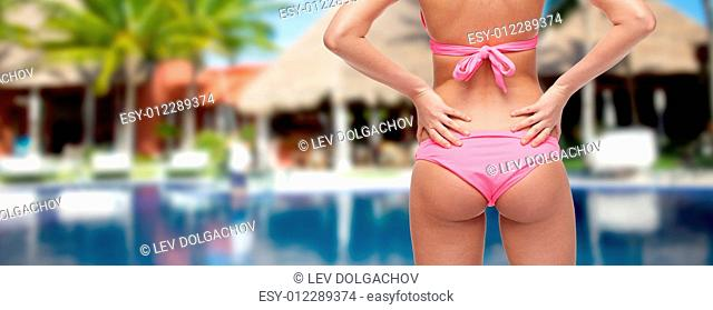 people, beauty, summer and travel concept - close up of young woman buttocks in pink bikini swimsuit over hotel resort with swimming pool