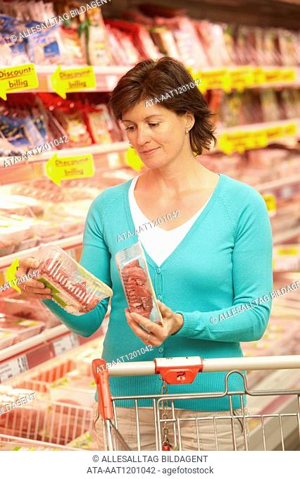 Woman buying fresh meat in the supermarket