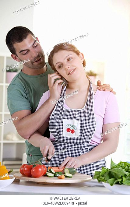 Man holding phone for cooking girlfriend