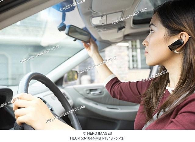 Woman adjusting rear-view mirror while driving car