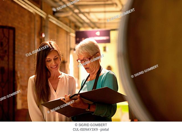 Two women looking at paperwork in wine cellar