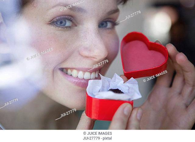 A woman holding a chocolate truffle in a heart-shaped box