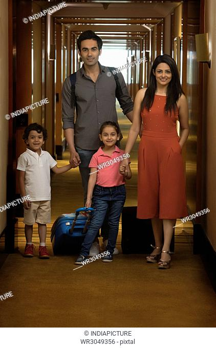 Family on vacation with trolley bag standing in hotel
