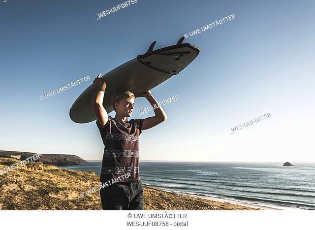Teenage boy carrying surfboard on head