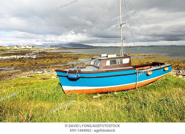 Fishing boat and cottages on island of Berneray in the Sound of Harris between North Uist and Harris  Outer Hebrides, Scotland