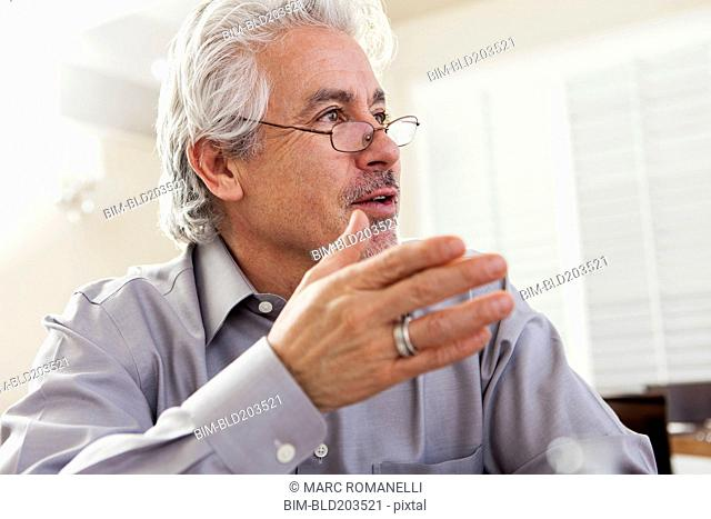 Hispanic businessman gesturing at desk