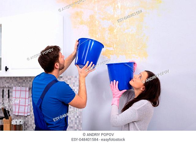 Young Woman And Repairman With Blue Bucket Collecting Water From Damaged Ceiling In Kitchen