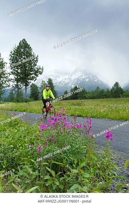 Woman riding a mountain bike on a path along the Richardson Highway near Valdez on an overcast day, Southcentral Alaska, Summer