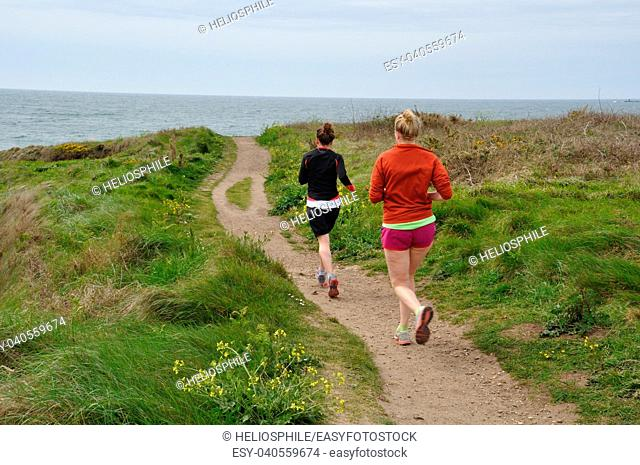 Joggers on the coastal path to Kersidan in Brittany