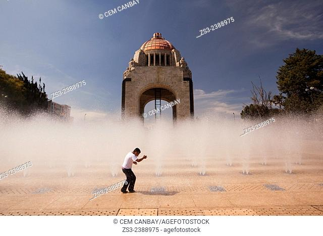 Student playing with the water near the Monument dedicated to the Mexican Revolution (Monumento dedicado a la Revoluci—n Mexicana) at night, Mexico City, Mexico