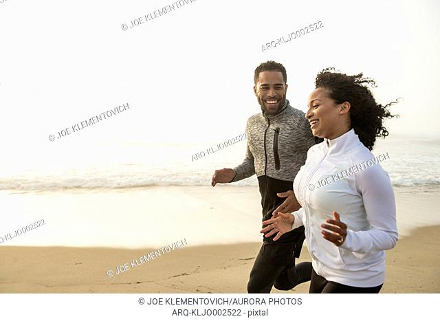 Man and woman jogging side by side on coastal beach and smiling, Hampton, New Hampshire, USA