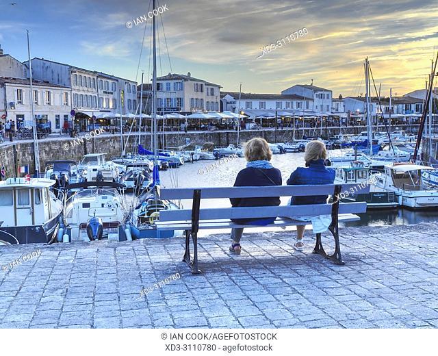 two women on a bench overrlooking the harbour, Saint-Martin-de-Re, Ile de Re, Charente-Maritime Department, Nouvelle Aquitaine, France