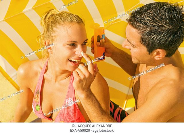 A young man covering his girlfriends nose with suntan lotion on a beach