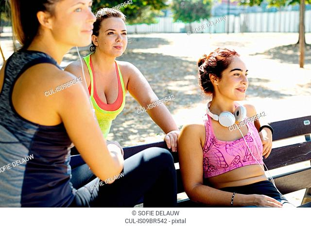 Friends taking break from exercise in park