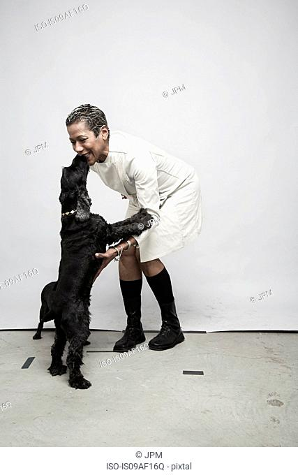Studio shot of mature woman having fun with pet dogs