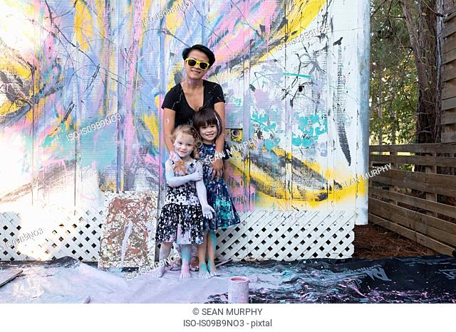 Mother and daughters covered in paint by painted wall