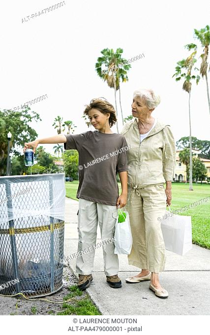 Boy and grandmother standing by trash can, boy throwing away drink can