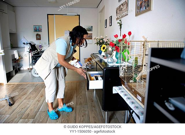 Rotterdam, Netherlands. A professional nurse of a Charlois nursing home searching a closet drawer for medical aids and devices beneficial to a senior adult...