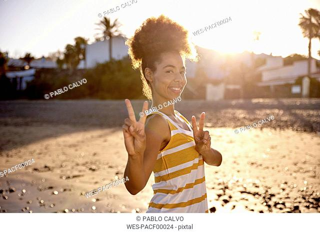 Portrait of woman showing victory sign on the beach