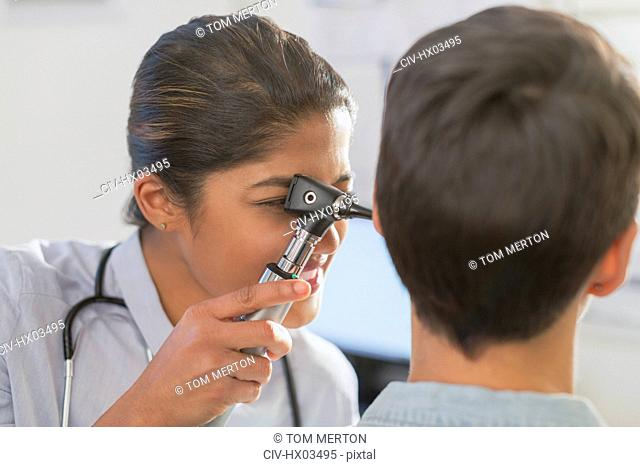 Female doctor using otoscope in ear of patient