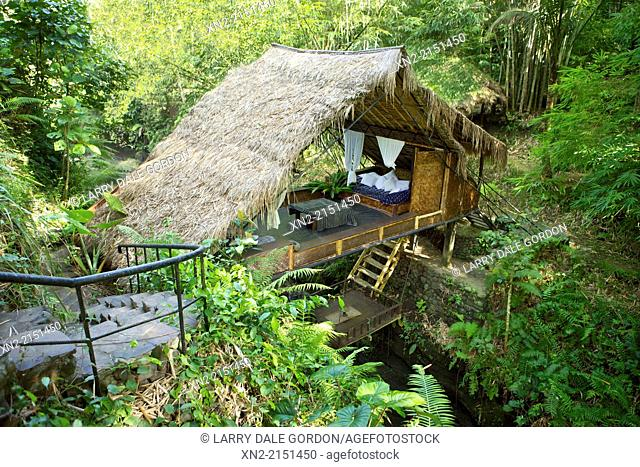 An outdoor room sits on a platform over a stream in the garden of a home in Ubud, Bali, Indonesia