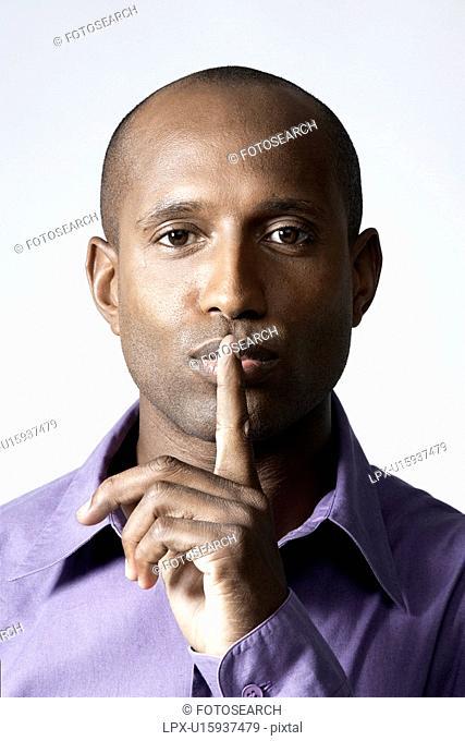 Mid adult man holding index finger on lips