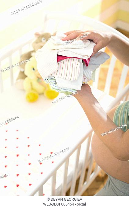 Pregnant woman holding stack of baby clothing