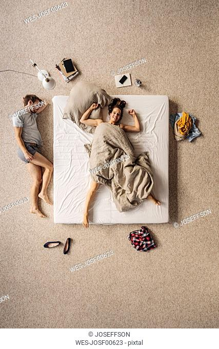 Happy woman lying in bed with man lying besides, top view