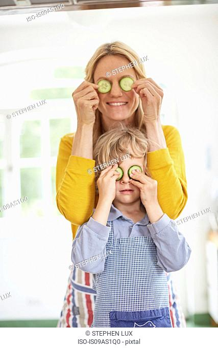 Mother and son covering eyes with cucumber slices