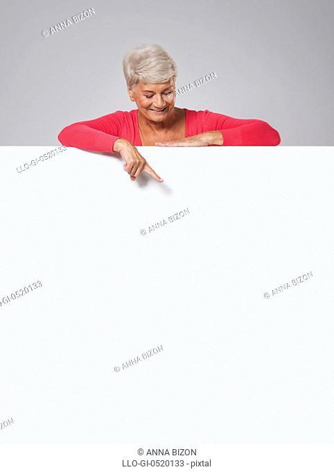 Senior woman peeking on whiteboard. Debica, Poland