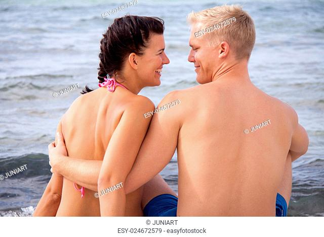 Happy romantic young couple enjoying a date at the seaside sitting arm in arm overlooking the ocean and looking back at the camera with charming happy smiles
