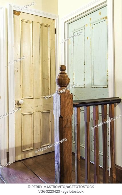 Wooden newel post and railing next to old faded white paint closet and blue bedroom doors on the upper floor hallway inside an old 1835 fieldstone house