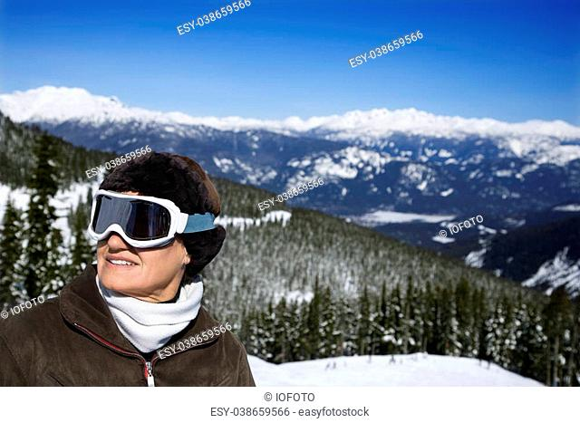 Caucasian middle-aged woman skier in goggles posing on mountain