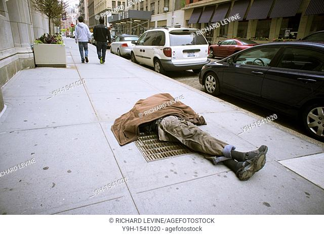 Homeless man sleeping on a vent in the sidewalk in Greenwich Village in New York With the deteriorating economy many worry about the return of crime and...