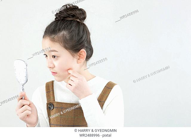 Side view portrait of school girl holding and looking in her hand mirror touching her face