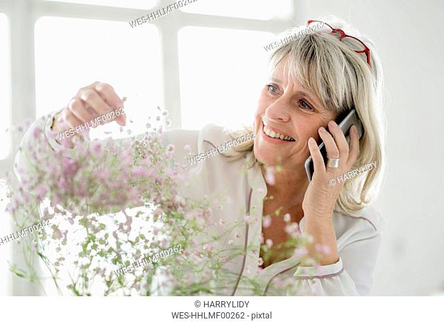 Smiling mature woman on cell phone caring for flowers