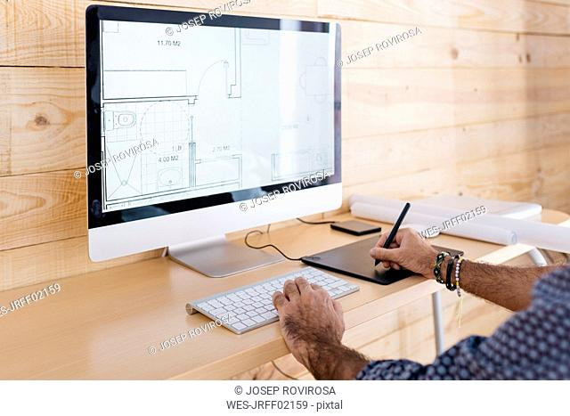 Close-up of man working on floor plan at home using the computer and graphics tablet
