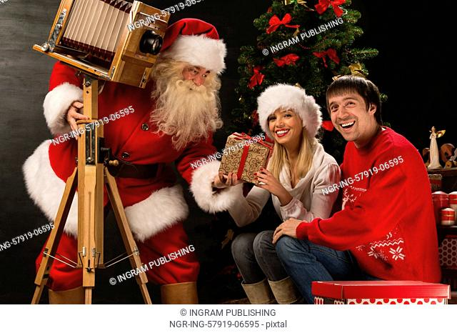 Santa Claus taking picture of couple with old wooden camera at home near Christmas tree