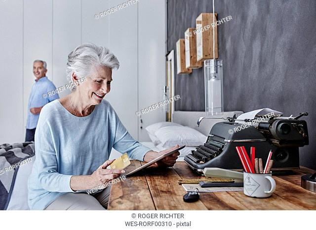 Smiling senior woman shopping online in bedroom with husband in background