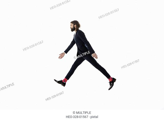 Businessman walking, striding against white background