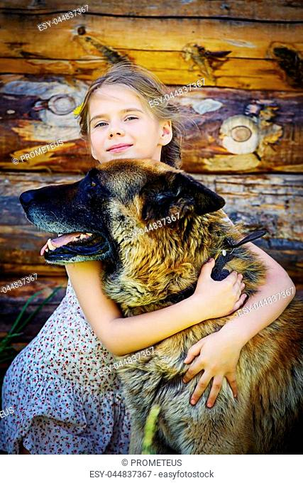 Cute little girl embraces her dog. Sunny summer day in the countryside