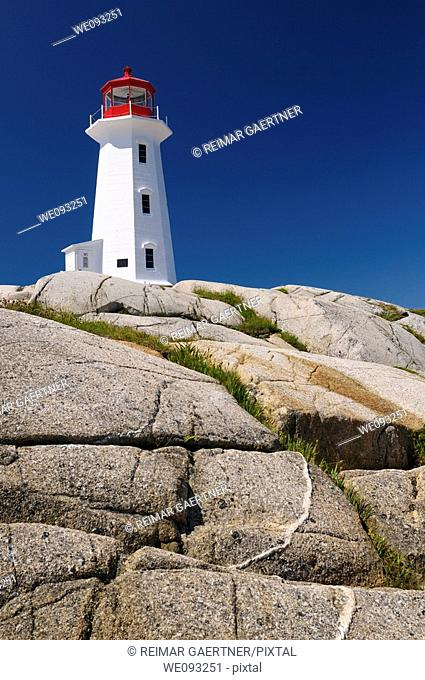 Peggys Cove lighthouse on smooth granite rocks against a blue sky Nova Scotia