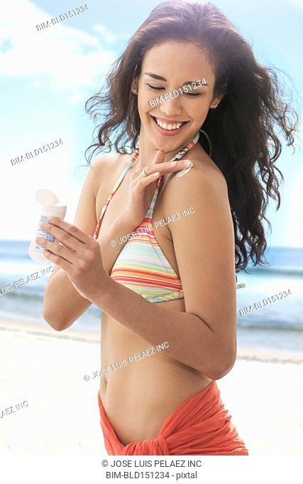 Mixed race woman applying sunscreen on beach