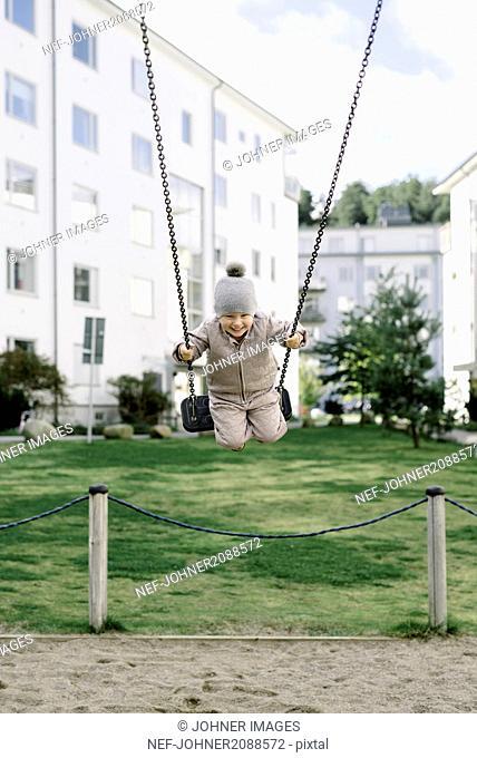 Boy having fun on swing in playground