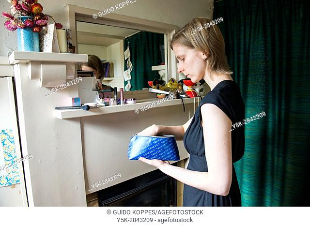 Tilburg, Netherlands. Classical singer and teacher doing her make-up while looking in her rehearsal room mirror