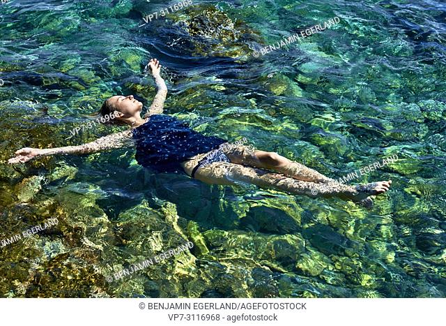 woman floating in sea water, wearing dress and slip, in holiday destination Chersonissos, Crete, Greece